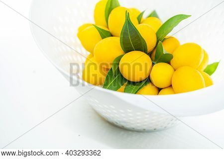 Close Up Fruit In Basket, Beautiful Marian Plum Bunch Or Plum Mango Bunch In Modern Plastic White Ba