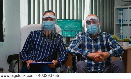 Businessman In Wheelchair And Coworker Wearing Visor Having Videomeeting In Business Office During G