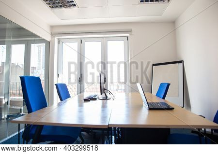 Empty Office Meeting Room. Boardroom With Conference Table, Flip Chart Computer And Laptop On Desk.