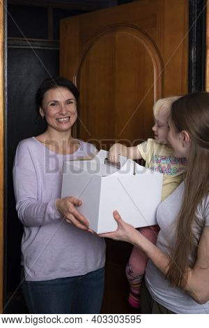 Happy Guest Brought A Box Of Cake. Young Mother And Child Welcome A Guest With A Gift.