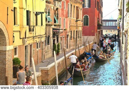 Venice, Italy - 5 August, 2016: Tourists Enjoying The Gondolas In A Canal. The Gondolas Are The Most