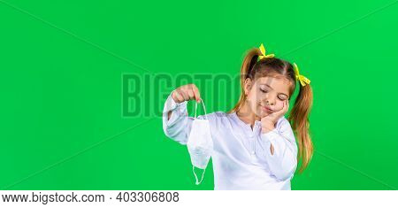 Banner. A Pensive Preschool Girl Holds A Medical Mask And Looks At It With Displeasure. Green Backgr