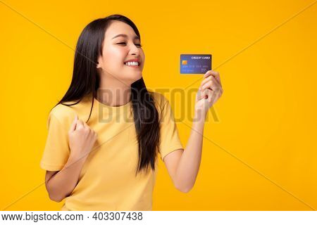 Happy Young Asian Woman Showing Plastic Credit Card And Looking At Credit Card With Happy Standing O
