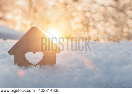 A Small Model Of A House With A Window In The Form Of A Heart Stands In The Snow Against The Backgro