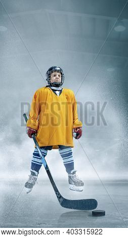 Strong. Little Hockey Player With The Stick On Ice Court And Smoke Background. Sportsboy Wearing Equ