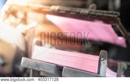 The Photo Effect With The Printing Press Machine Takes Sheet Of Paper In Action In The Printing Prod