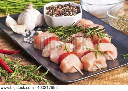 Fresh Chicken Kebab.raw Chicken Skewers On Skewers On A Black Plate With Spices And Green Rosemary,