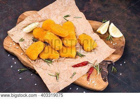 Breaded Nuggets On A Wooden Kitchen Board With Chili And Lemon Wedges. Convenience Food, Precooked.f