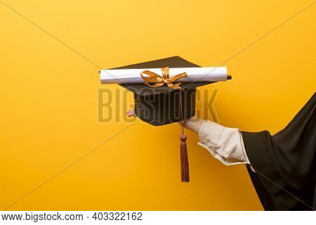 Close Up Of Woman Hand In Graduation Gown Is Holding Graduation Cap And Certificate On Yellow Backgr