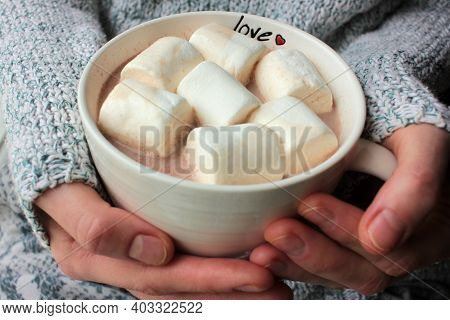 Person In Gray Sweater Holding A Cup Of Hot Or Cocoa With Marshmallows. Woman Hands Holding A Mug Wi