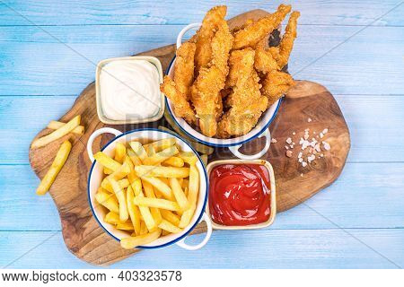 Fried Chicken Dippers In Bucket With Sauce On Blue Background.chicken Breaded Strips In Small Cerami