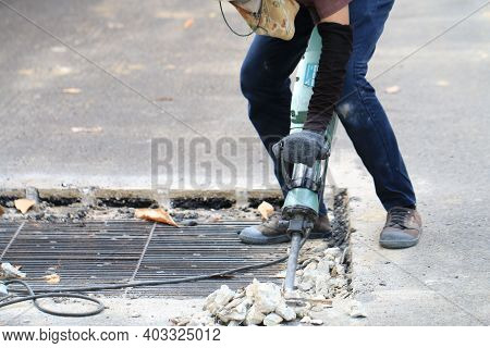 Male Workers Use Electric Concrete Breaker For Digging And Drilling Concrete Repairing Driveway Surf