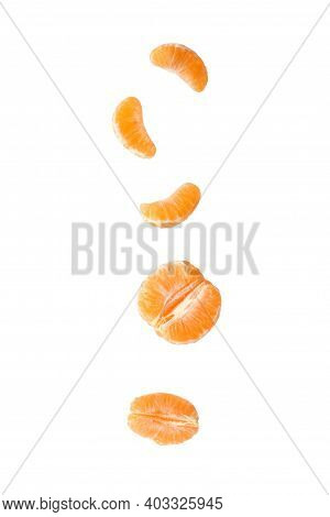 Bright Tangerine On A Clean Background. Tangerine Slices. Peeled Tangerine. Citrus In Flight