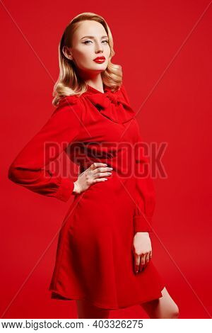 Portrait of a stunning blonde woman in red dress on a red background. Love and Valentine's Day concept. Beauty and fashion. Make-up and cosmetics.