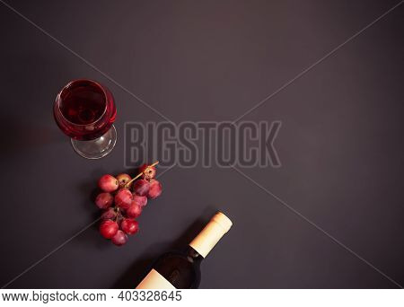 Glass Of Red Wine, Purple Grape And Bottle Of Red Wine On Dark Background. Top View With Copy Space.