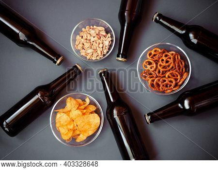 Brown Glass Bottles Of Beer And Beer Snacks On Gray Background. Top View.