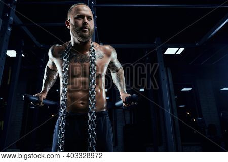 From Below View Of Athletic Young Man With Perfect Muscular Shirtless Body Doing Triceps Dips On Par
