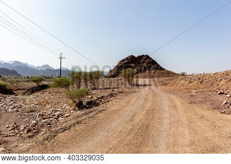 Rural Gravel Road In Hatta Village In Hajar Mountains In United Arab Emirates With Barren Land And D