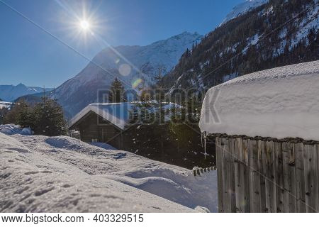 Winter Landscape With Wooden House In Snowy Mountains. Sunny Winter Day In Alps. Christmas Holiday A