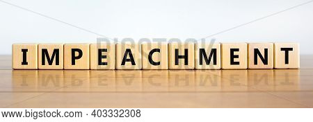 Impeachment Symbol. Wooden Cubes With The Word 'impeachment'. Beautiful Wooden Table, White Backgrou