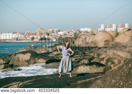 The dancer woman is engaged in choreography on the rocky coast of the ocean.