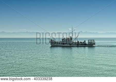A Ship With Passengers Floats On Lake Baikal Against The Backdrop Of A Mountain Landscape. Russia