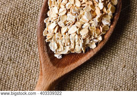 Oat Flakes On Wooden Spoon. Healthy Breakfast Background. Empty Copy Space Food Background. Porridge