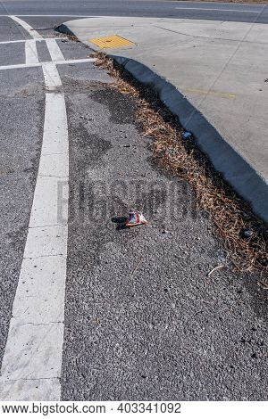 Discarded Snack Chips Bag Laying Alongside The Curb In The Roadway Along With Other Debris Polluting