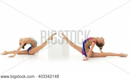 Two Cute Little Girl Gymnast In A Beautiful Sports Swimsuit Performs A Gymnastic Element, Twine On B