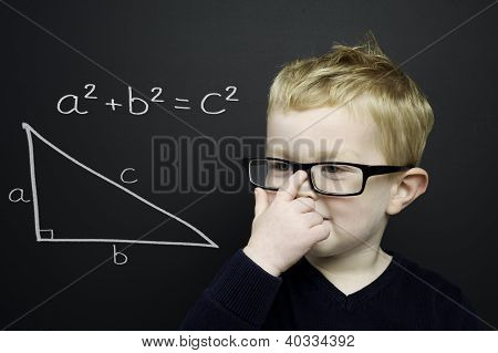 Smart Young Boy Stood Infront Of A Blackboard