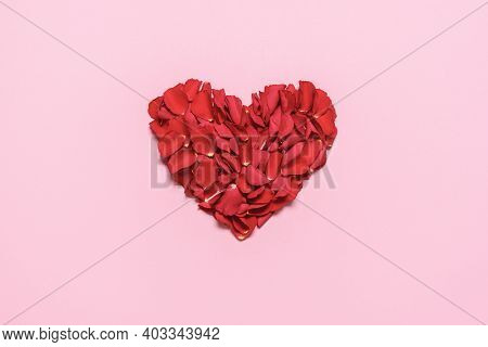 Valentine Day Heart Made Of Rose Petals, Isolated On Pink Background. Flat Lay With A Romantic Red H