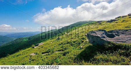 Mountain Meadow On A Sunny Morning. Cloud Rolling Above The Hill With Rocks Among The Grass. Warm Su