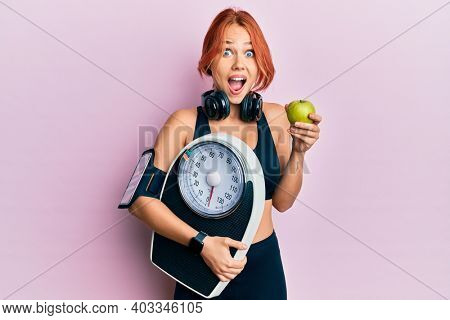 Young beautiful redhead woman holding weight machine to balance weight loss celebrating crazy and amazed for success with open eyes screaming excited.