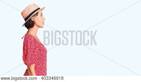 Young beautiful woman wearing summer hat looking to side, relax profile pose with natural face with confident smile.