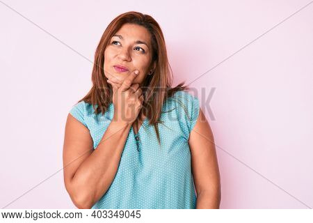 Middle age brunette hispanic woman wearing casual clothes with hand on chin thinking about question, pensive expression. smiling with thoughtful face. doubt concept.