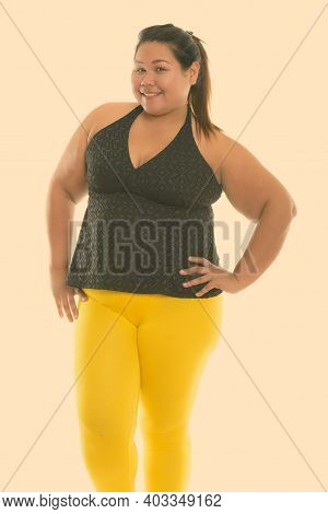 Studio Shot Of Young Happy Fat Asian Woman Smiling And Standing Ready For Gym