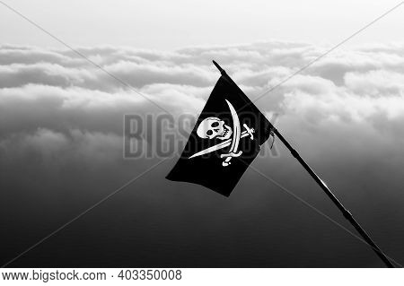 Jolly Roger - Pirate Flag On Wind And Sea In Cloudy Sky At Background. Black And White Toned Image.