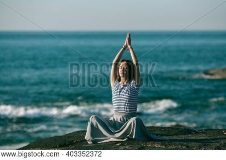Woman meditating on the sea beach during a wonderful sunrise. Yoga and fitness.
