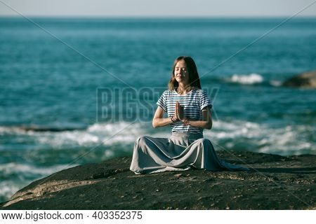A girl meditating on the sea beach during a wonderful sunrise. Yoga and fitness.