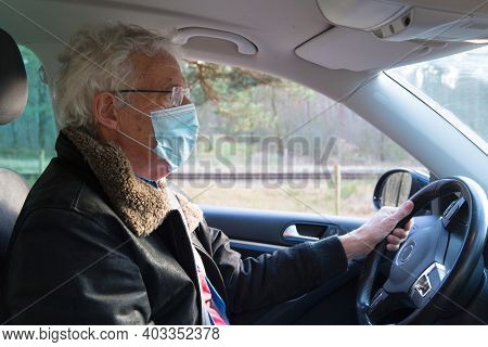 Elder man with facemask in car on the road