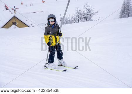 Blurred Focus Background. A Boy Lifting On The Ski Drag Lift Rope In Bright Sport Outfit On The Ski