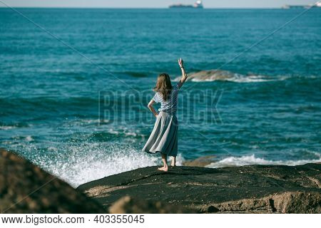 The dancer girl is engaged in choreography on the ocean coast.