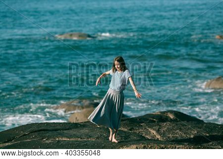 A girl is engaged in choreography on the ocean coast.