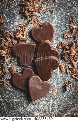 Sweet chocolate hearts on black table. Top view.