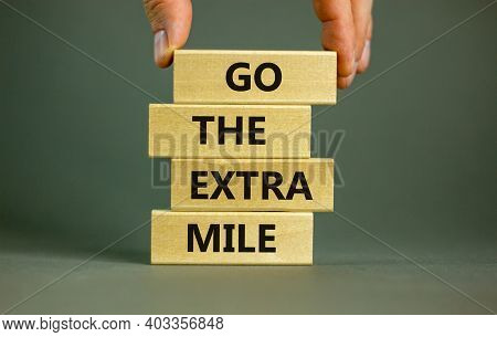 Go The Extra Mile Symbol. Wooden Blocks With Words 'go The Extra Mile'. Male Hand. Beautiful Grey Ba