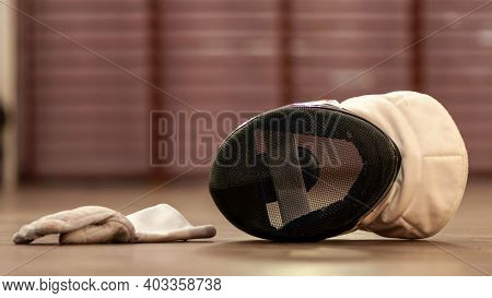 A Fencing Mask And A Fencing Glove On The Floor