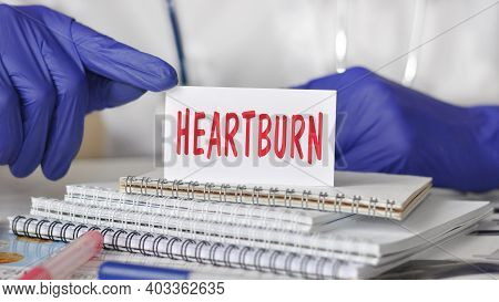 Doctor Holding A White Paper Card With Text: Heartburn. Healthcare Conceptual For Hospital, Clinic A