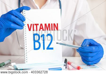 Doctor Holding A White Card In Hands And Pointing The Word Vitamin B12. Healthcare Conceptual For Ho