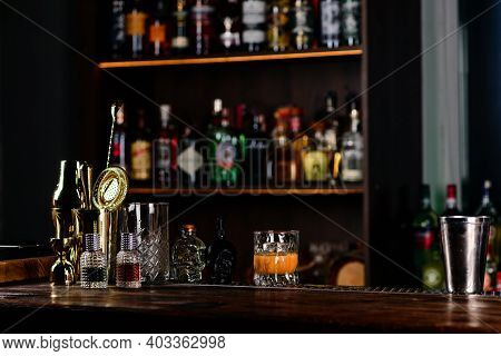 Empty Top Of Wooden Counter Bar And Blurred Bottles. Background For Your Product Display. Empty Bar