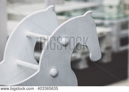 Old White Wooden Hobby-horse Against A Playground